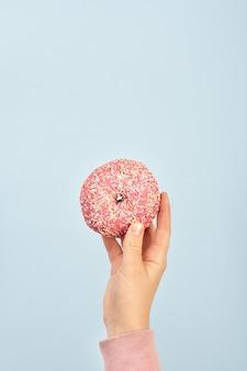 Vista frontal de la mano que sostiene donut glaseado con chispas