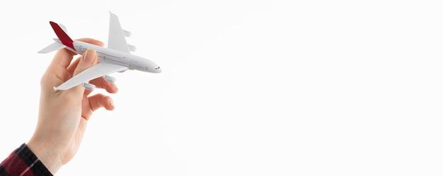 Vista frontal de la mano que sostiene la figurilla de avión con espacio de copia