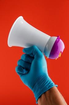 Vista frontal de la mano que sostiene el megáfono mientras usa guante