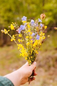 Vista frontal de la mano que sostiene el ramo de flores