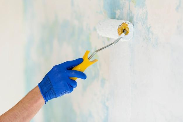 Vista frontal de la mano que sostiene el rodillo de pintura