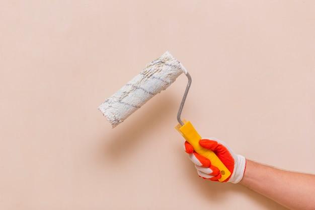 Vista frontal de la mano que sostiene un rodillo de pintura
