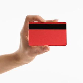 Vista frontal de la mano que sostiene la tarjeta de crédito