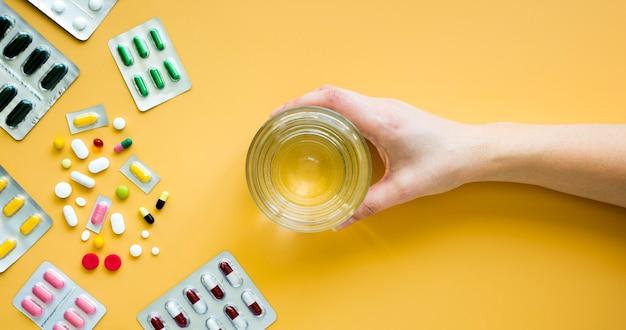 Vista frontal de la mano que sostiene un vaso de agua con pastillas y láminas