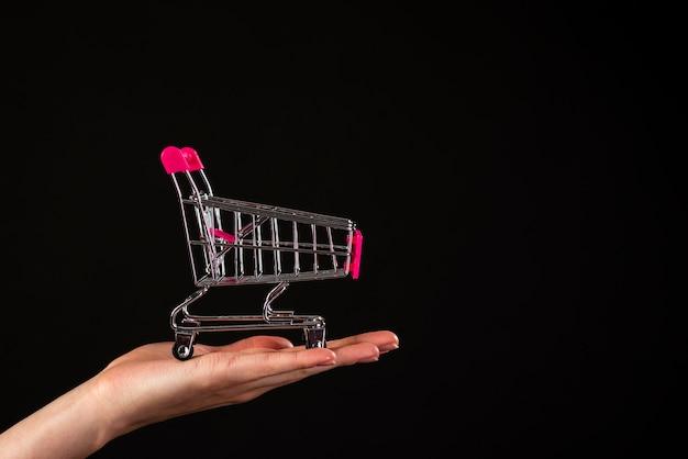 Vista frontal de una mano sosteniendo un mini carrito de compras sobre un fondo negro