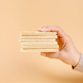 Vista frontal de la mano sujetando obleas con espacio de copia