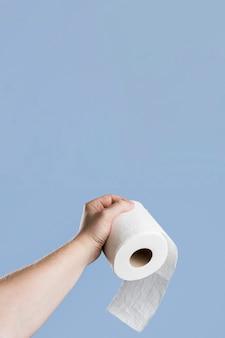 Vista frontal de la mano sujetando papel higiénico con espacio de copia