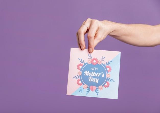 Vista frontal mano con tarjeta de felicitación