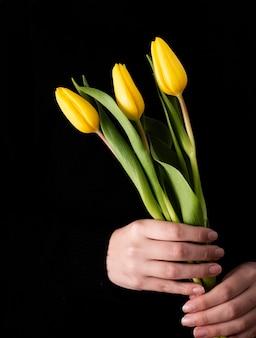 Vista frontal de la mano con tulipanes amarillos