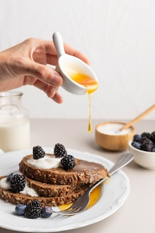 Vista frontal de la mano vertiendo miel sobre tostadas con arándanos