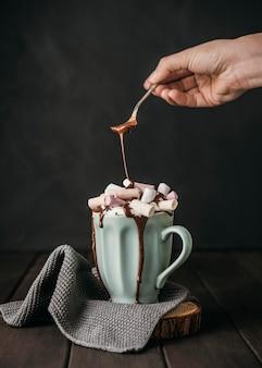 Vista frontal mano vertiendo salsa de chocolate sobre malvaviscos
