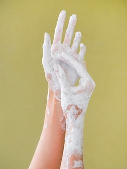 Vista frontal de manos cubiertas de pintura