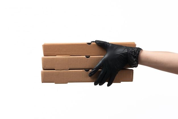 Una vista frontal manos femeninas en guantes negros con cajas de entrega en blanco