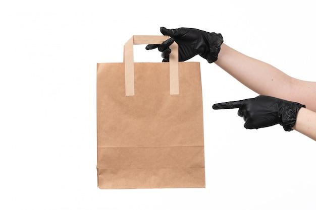 Una vista frontal manos femeninas con guantes negros con paquete de alimentos de papel en blanco