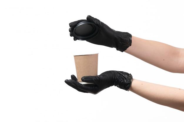 Una vista frontal manos femeninas en guantes negros con taza de café abriendo su tapa en blanco