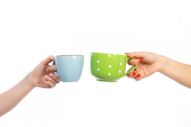 Una vista frontal manos femeninas que sostienen tazas de diferentes colores en el blanco