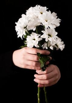 Vista frontal manos con flores de primavera