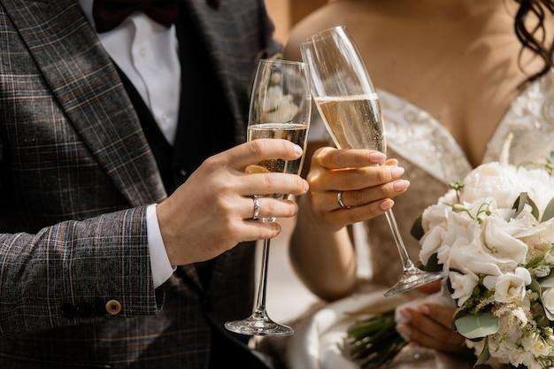 Vista frontal de las manos de los novios con copas de champán y bouquet de bodas