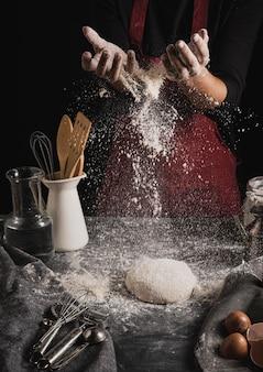 Vista frontal manos de panadero untando harina