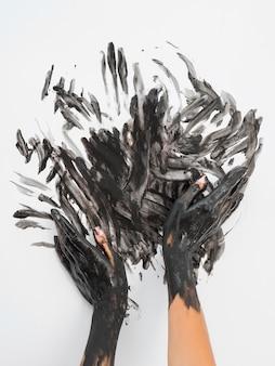 Vista frontal de manos con pintura negra