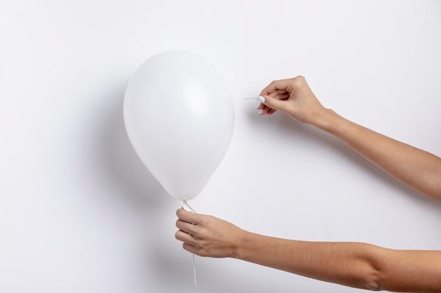 Vista frontal de las manos sosteniendo la aguja tratando de hacer estallar el globo