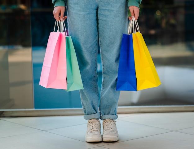 Vista frontal manos sosteniendo bolsas de compras