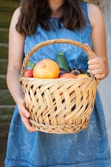 Vista frontal manos sosteniendo la cesta con verduras
