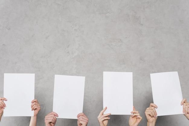 Vista frontal de manos sosteniendo papeles en blanco con espacio de copia