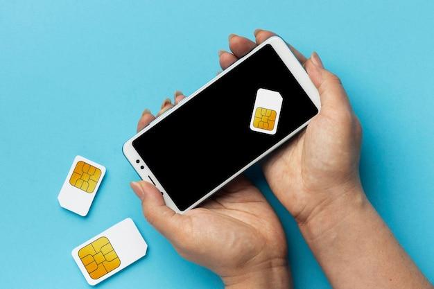 Vista frontal de manos sosteniendo tarjetas sim de teléfonos inteligentes
