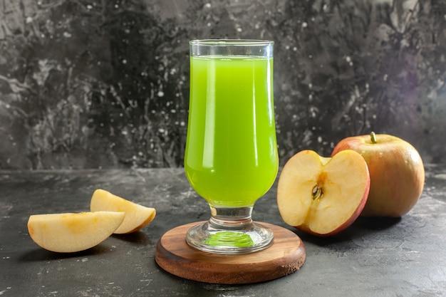 Vista frontal de la manzana madura fresca con jugo de manzana verde en el color de la foto del árbol de jugo suave oscuro