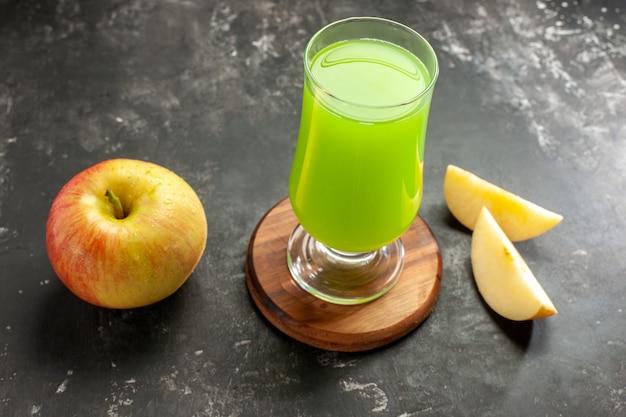 Vista frontal de la manzana madura fresca con jugo de manzana verde en el color de la foto de jugo suave oscuro