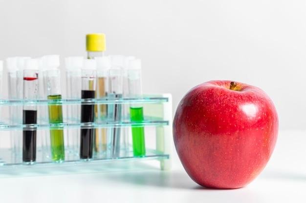 Vista frontal manzana roja y productos químicos verdes