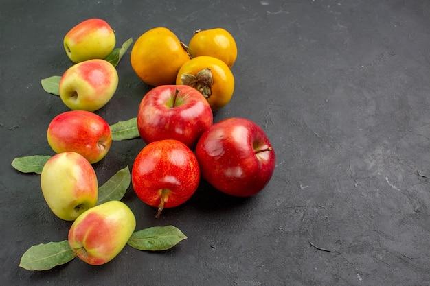 Vista frontal de manzanas frescas con caquis en mesa oscura árbol suave maduro fresco
