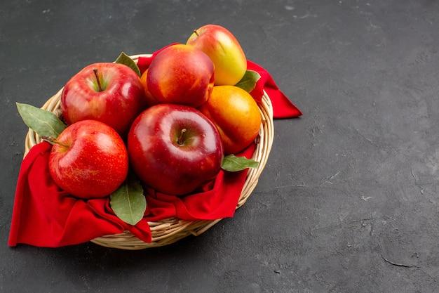 Vista frontal de las manzanas frescas dentro de la canasta en una mesa oscura árbol frutal fresco maduro