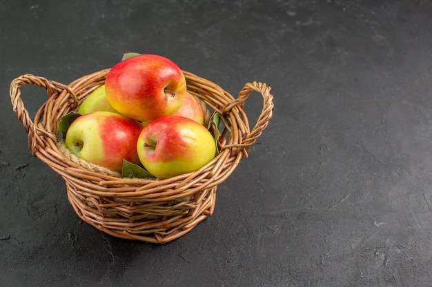 Vista frontal de las manzanas frescas frutas maduras dentro de la canasta en la mesa gris fruta fresca del árbol