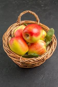 Vista frontal de las manzanas frescas frutas maduras dentro de la canasta en el piso gris árbol de frutas frescas maduras