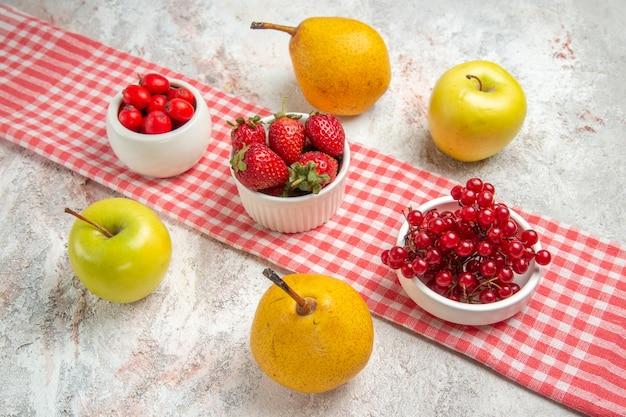 Vista frontal de manzanas frescas con frutos rojos y peras en el árbol de baya de fruta de mesa blanca