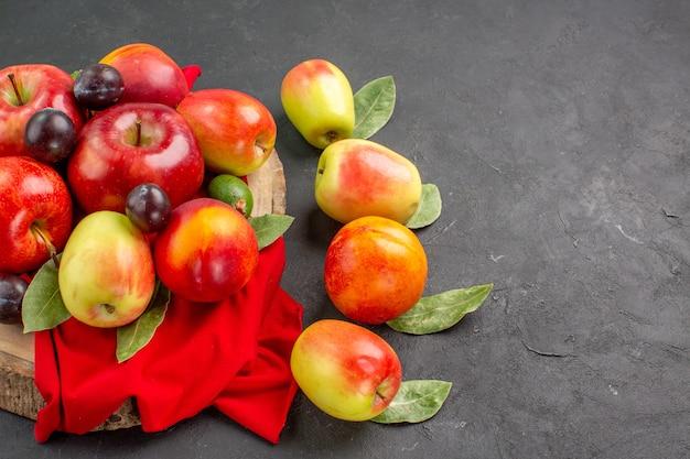 Vista frontal de manzanas frescas con melocotones y ciruelas en el árbol de jugo de mesa oscura madura suave