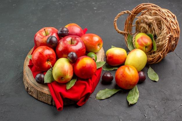 Vista frontal de manzanas frescas con melocotones y ciruelas en el árbol de jugo de mesa oscura suave