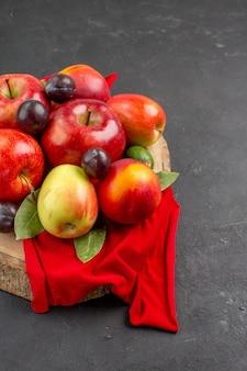 Vista frontal de manzanas frescas con melocotones y ciruelas en la mesa oscura árbol de jugo suave maduro