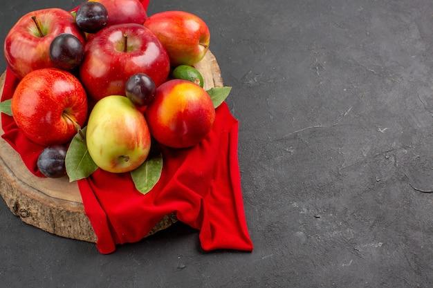 Vista frontal de manzanas frescas con melocotones y ciruelas en piso oscuro árbol de jugo suave maduro