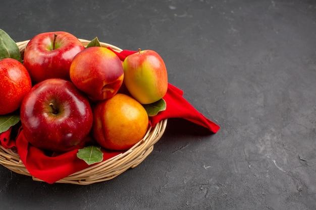 Vista frontal de las manzanas frescas con melocotones dentro de la cesta en el árbol de la mesa oscura frutas frescas maduras