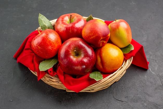 Vista frontal de las manzanas frescas con melocotones dentro de la cesta en la mesa oscura árbol fruta fresca madura