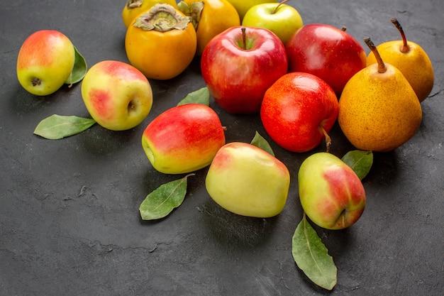 Vista frontal de manzanas frescas con peras y caquis en mesa oscura madura fresca suave