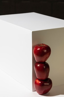 Vista frontal de manzanas rojas apiladas junto al podio