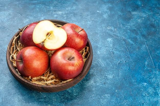 Vista frontal de las manzanas rojas frescas dentro de la placa sobre la superficie azul
