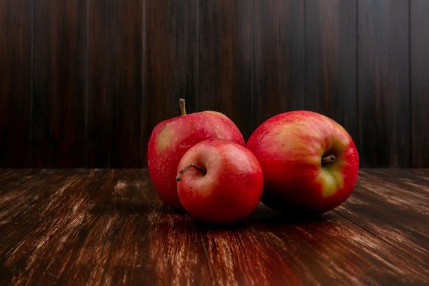 Vista frontal de manzanas rojas sobre un fondo de madera