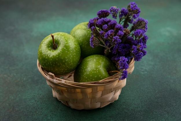 Vista frontal de manzanas verdes en una canasta con flores de color púrpura sobre un fondo verde