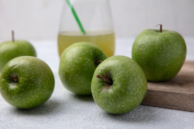Vista frontal de manzanas verdes con jugo de manzana en un vaso sobre un fondo blanco.