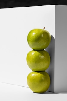 Vista frontal de manzanas verdes junto al podio